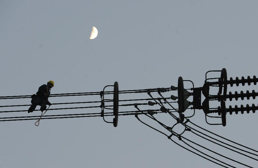 12月5日,在安徽省青阳县步岭村,电力职工在90多米的高空对向家坝至上海800千伏特高压直流输电线路安徽段的线路进行检修。 从12月1日起,国家电网公司组织员工对世界上电压等级最高、输送容量最大的直流输电工程向家坝至上海800千伏高压直流输电线路进行冬季安全检修,以提高该线路抗击恶劣天气的能力和确保春节期间供电,预计检修工作将于12月7日结束。  新华社发(宋卫星 摄)
