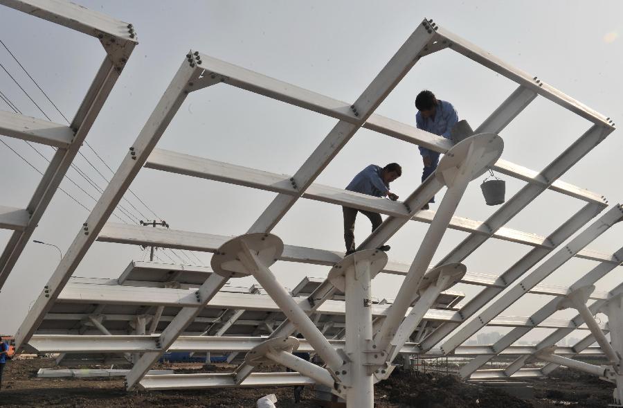 5月23日,工作人员在调整光伏支架。 由中铁电气化局承建的中新天津生态城中央大道光伏发电项目近期正在加紧建设。该项目位于生态城区中央大道西侧50米宽绿化带内,整体长约2.87公里,工程设计总容量为3.3兆瓦。工程施工包含土建桩基、基础承台、电缆沟、检修通道等。安装工程包括光伏支架及光伏板、逆变器及汇流箱安装、直流电缆铺设接线及接地工程等。新华社记者 岳月伟 摄